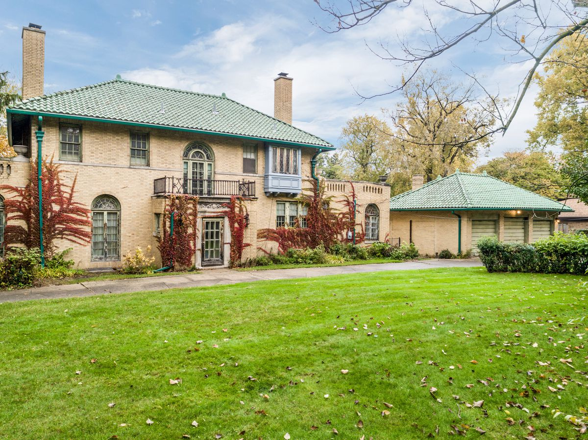 The rear of the house has red leafy vines climbing up its sides and a big green lawn. The three-car garage has the same cream-colored brick and green roof.