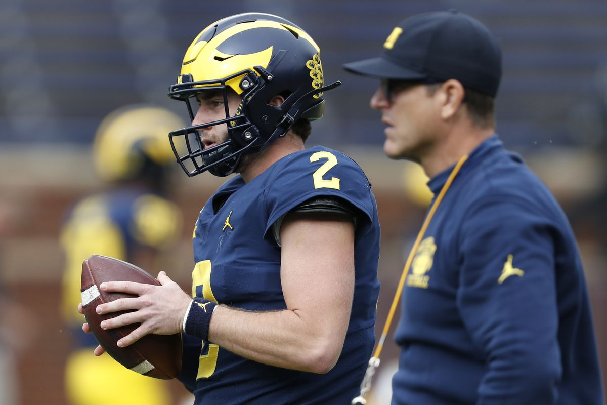 Michigan Wolverines quarterback Shea Patterson warms up near head coach Jim Harbaugh before the game against the Rutgers Scarlet Knights at Michigan Stadium.