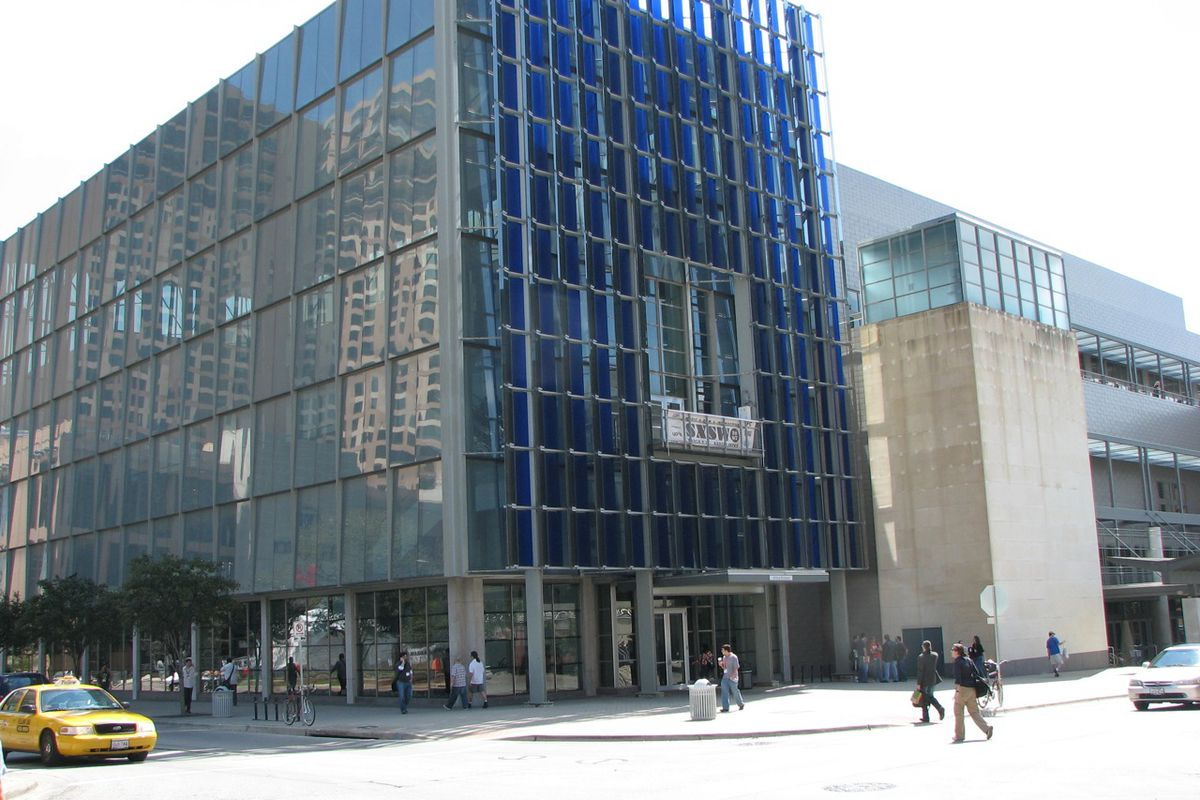 Exterior of seven-story glass and concrete building, photo shot from corner across the street.