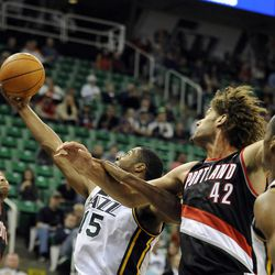 Utah Jazz power forward Derrick Favors (15) grabs a rebound between Portland Trail Blazers shooting guard Will Barton (5) and Portland Trail Blazers center Robin Lopez (42) in the second half of a game at the Energy Solutions Arena on Wednesday, October 16, 2013.