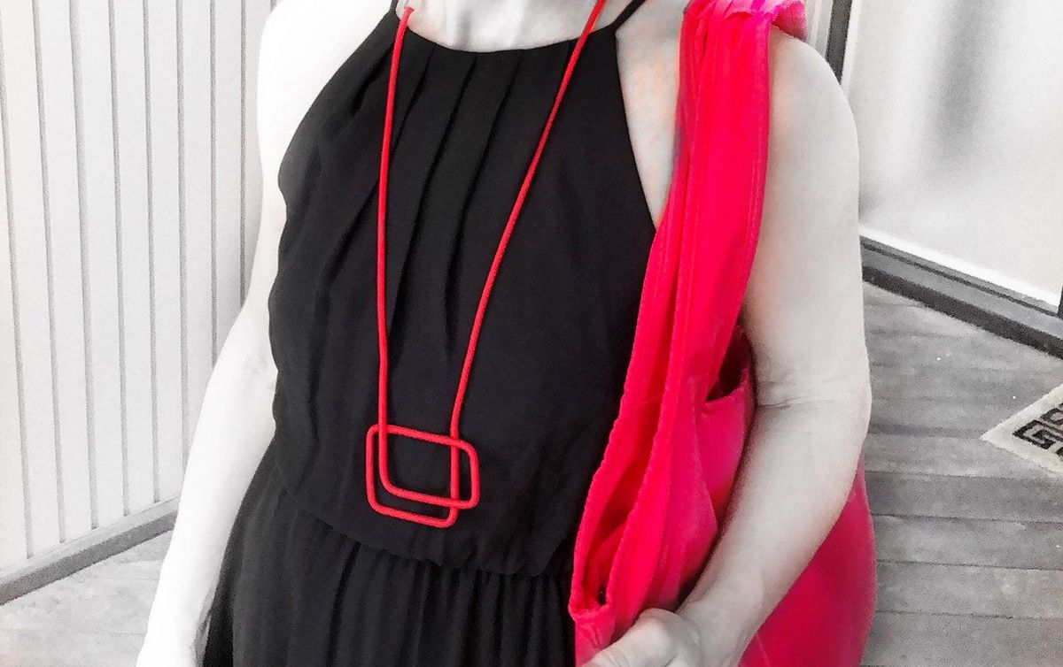 Woman in a black dress wears a red necklace with two square shapes.
