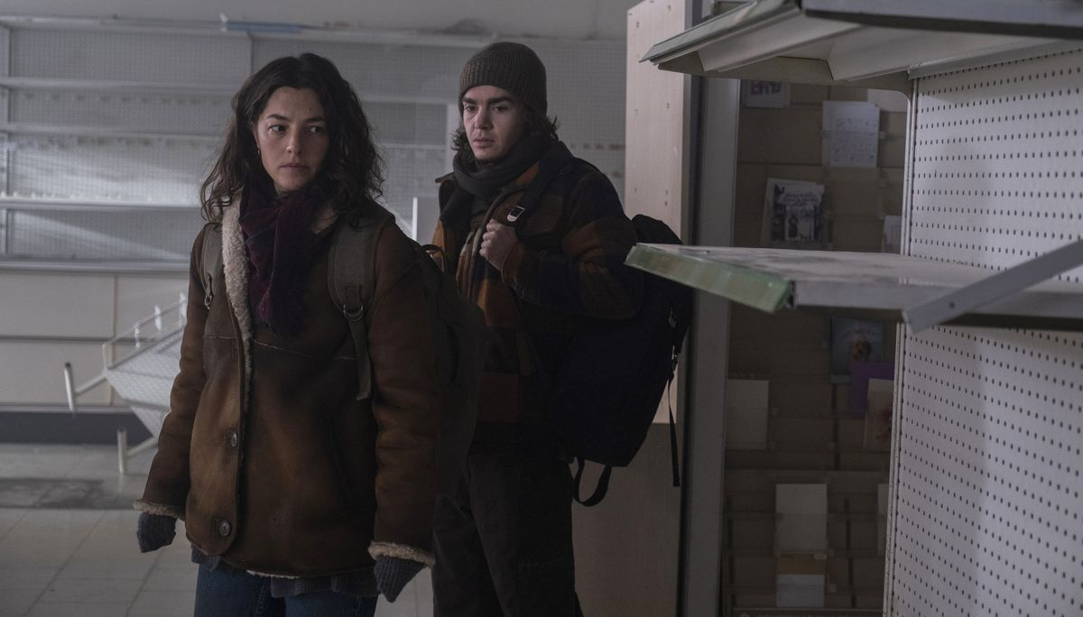 Olivia Thirlby as heroine and Elliot Fletcher as Sam enter a ransacked shop full of empty shelves in Y: The Last Man