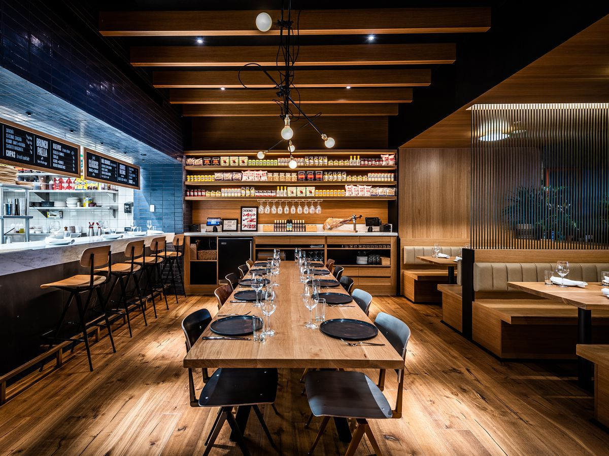 Boqueria's dining room, with tapas seating to the left, banquette seating to the right, and a pantry area in the background with a leg of jamon.