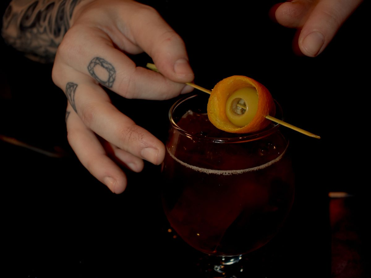 A tattooed hand serves up a brown-colored cocktail garnished with an orange peel.