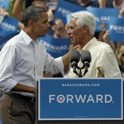 President Obama, left, talks with former Florida Gov. Charlie Crist at a campaign rally Saturday, Sept. 8, 2012, in Seminole, Fla.