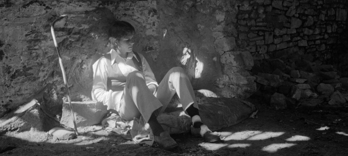 Bill Paxton sits on the ground next to a stone wall in the black-and-white film Taking Tiger Mountain