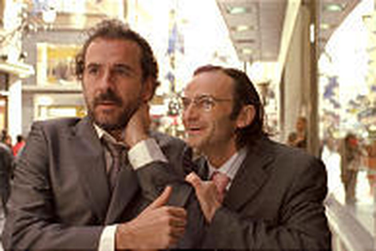 Rafael (Guillermo Toledo) is pulled into store by Alonso (Fernando Tejero).