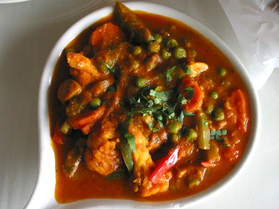 A bird's eye view of an Indian dish with tomato sauce and vegetables.