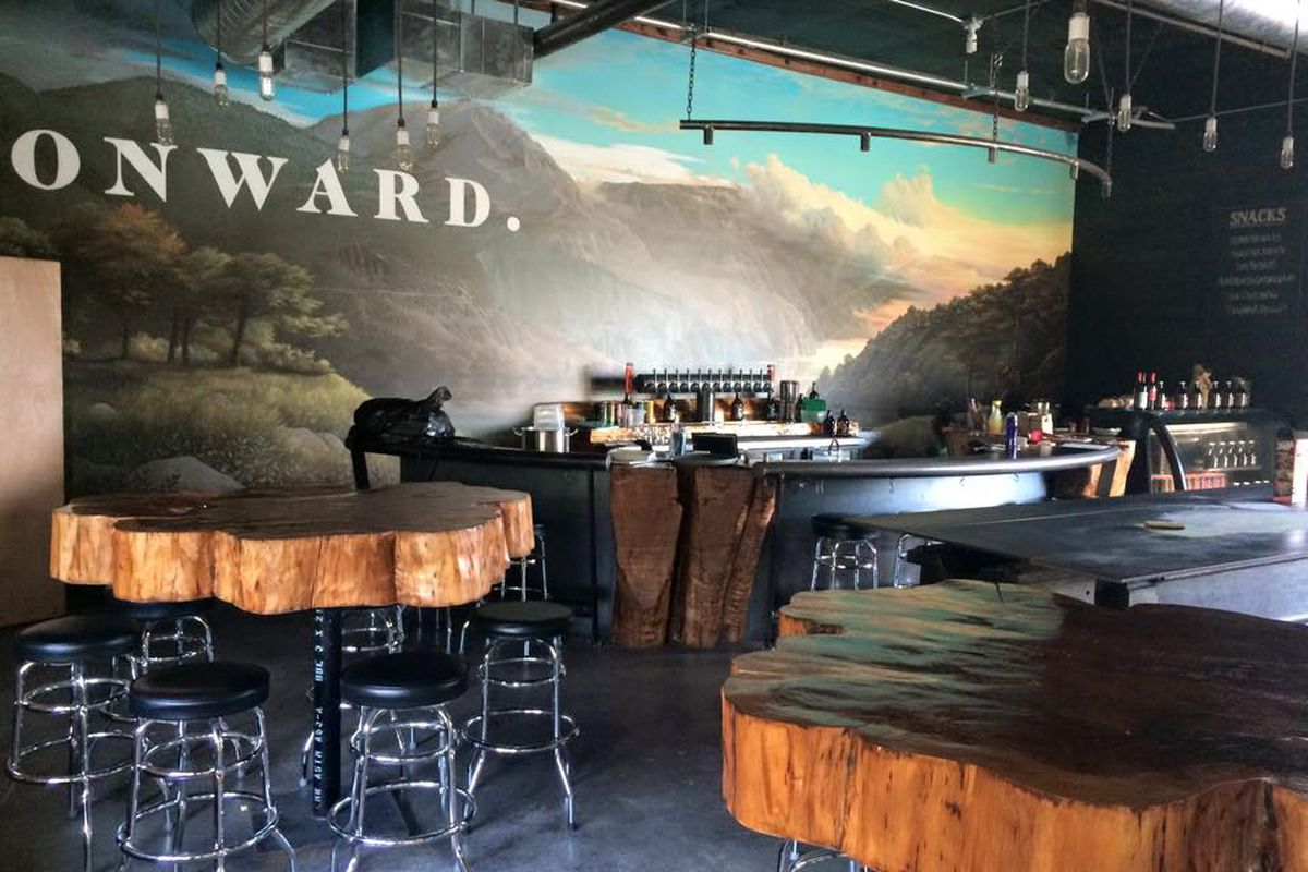 """The interior of Citizen Six, with wood tables and a mountain backdrop that reads """"Onward."""""""