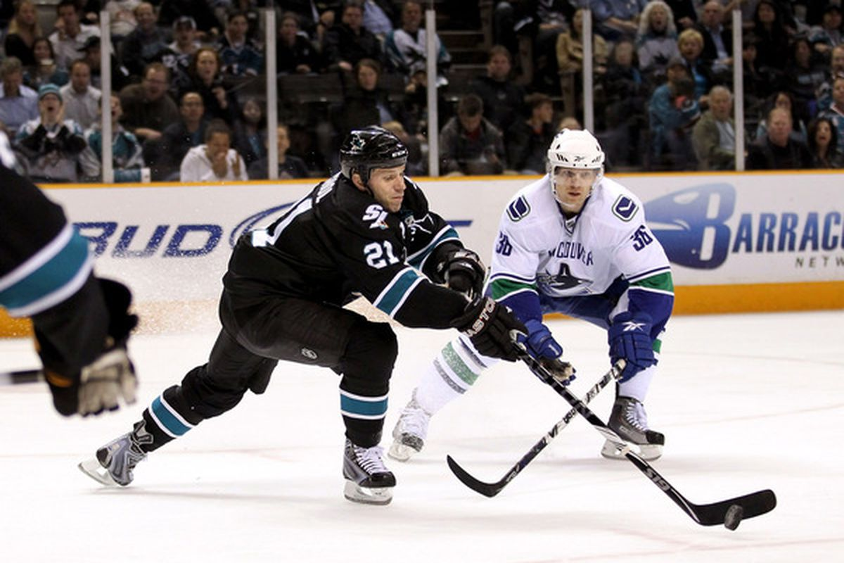 SAN JOSE, CA - APRIL 08:  Scott Nichol #21 of the San Jose Sharks and Jannik Hansen #36 of the Vancouver Canucks go for the puck at HP Pavilion on April 8, 2010 in San Jose, California.  (Photo by Ezra Shaw/Getty Images)