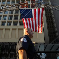 A member of the Chicago Fire Department passes by an American flag hoisted by two fire trucks during the commemoration of the 20th anniversary of 9/11 at the Richard J. Daley Plaza in the Loop, Saturday morning, Sept. 11, 2021.
