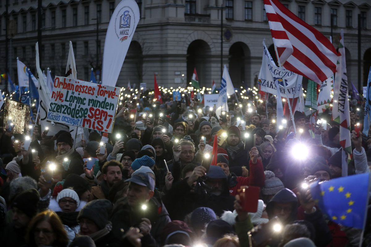 A group of protesters hold signs, candles, and flags in an anti-government demonstration in Budapest.