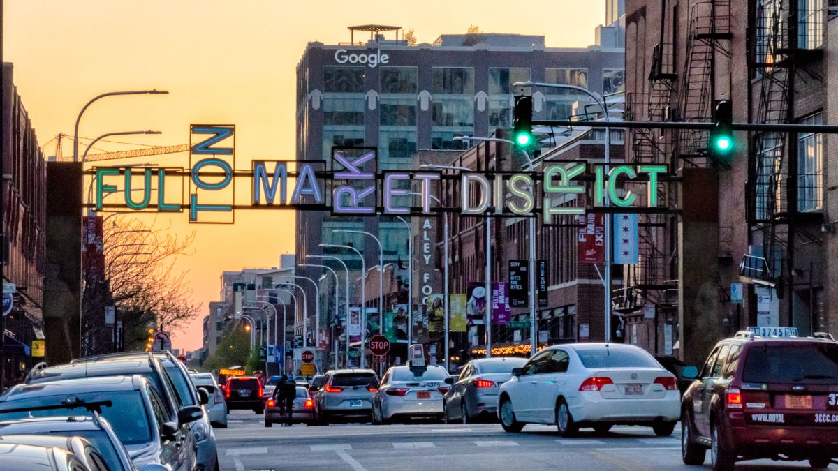 An image of Fulton Market Street with a neon gateway sign at sunset.