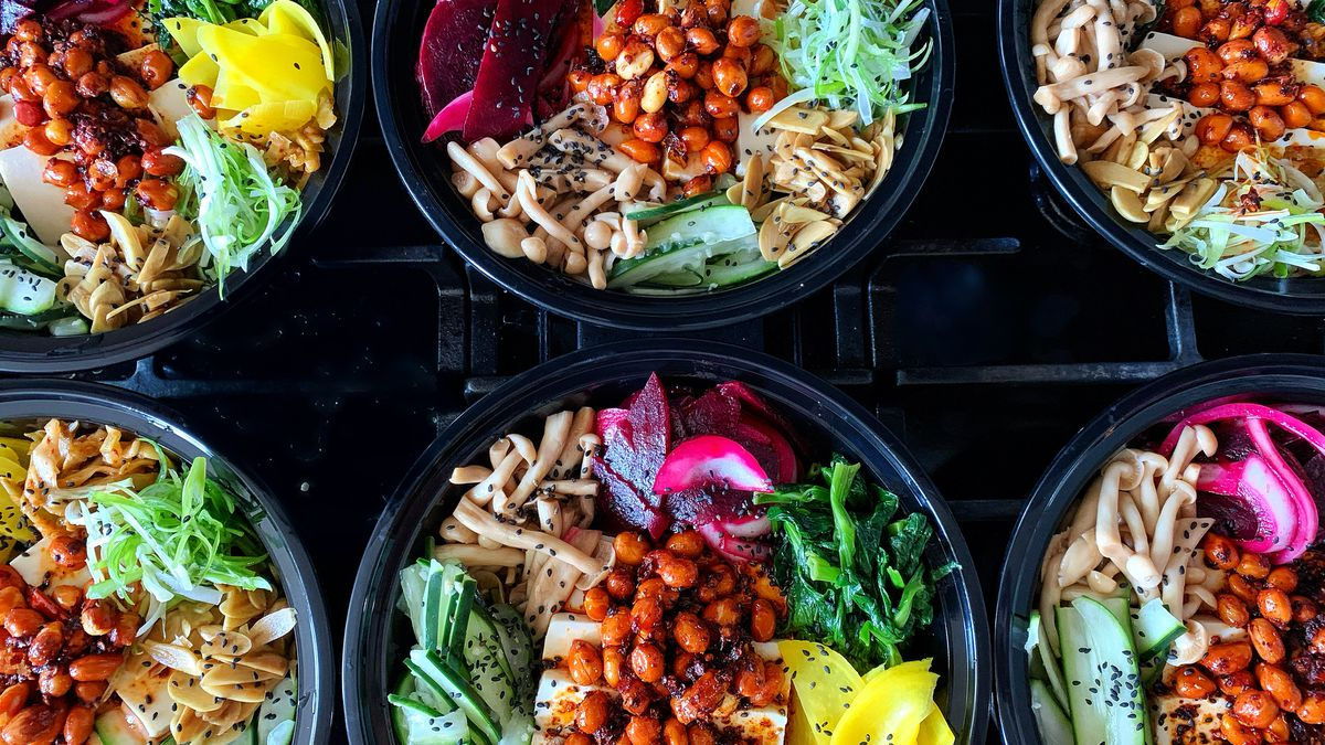 Two rows of colorful food in black, plastic takeout containers.