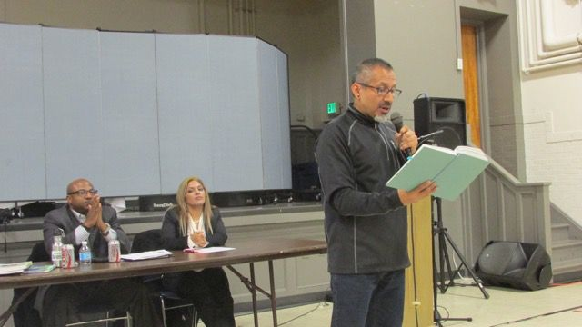 Olivos reads a passage about parent engagement from a book at Thursday's event.