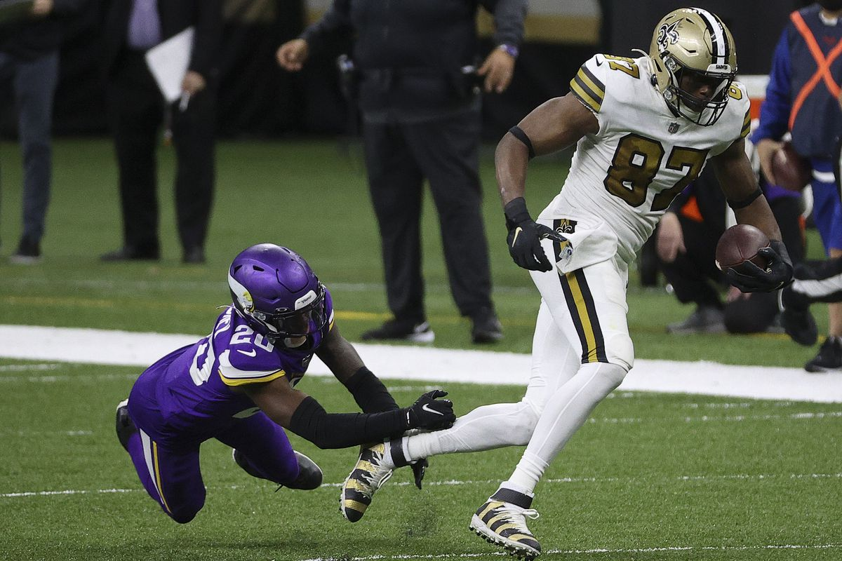 Jared Cook #87 of the New Orleans Saints makes a reception past Jeff Gladney #20 of the Minnesota Vikings at Mercedes-Benz Superdome on December 25, 2020 in New Orleans, Louisiana.