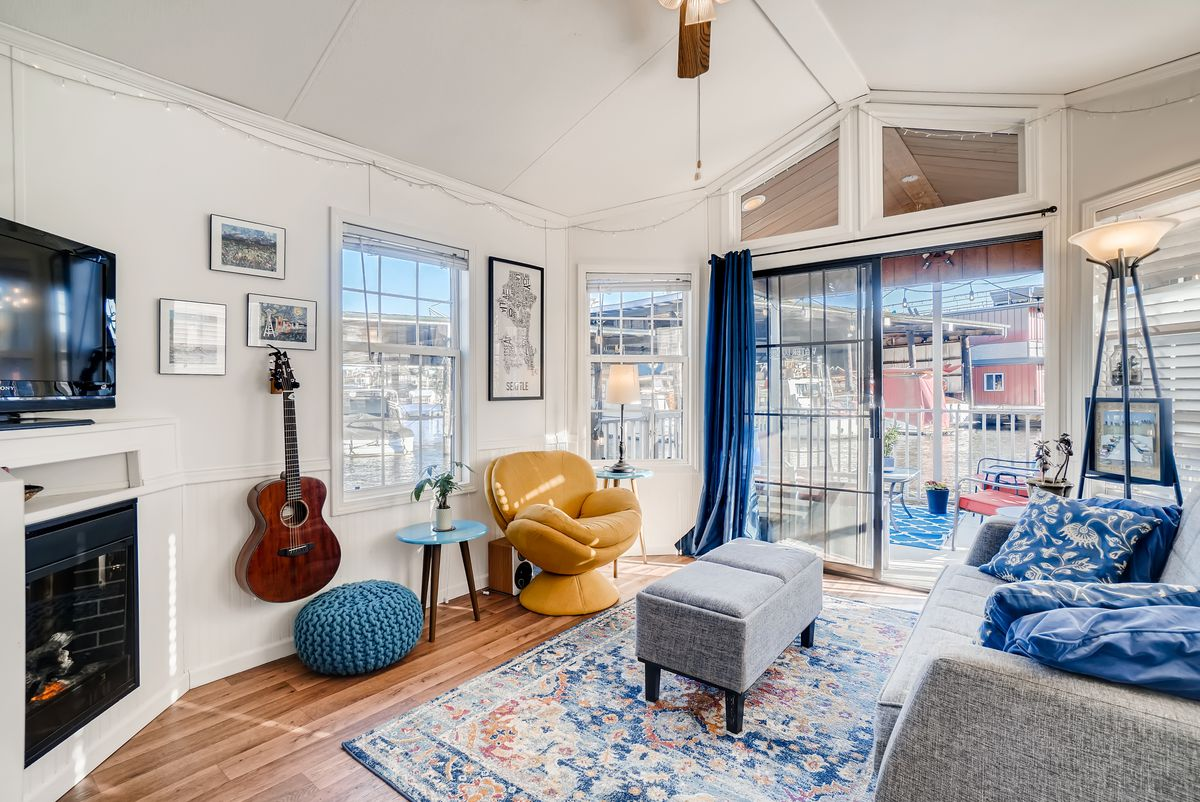 An interior view of the houseboat's living room. There are vaulted white ceilings, a fireplace, a gray couch, and a blue rug.