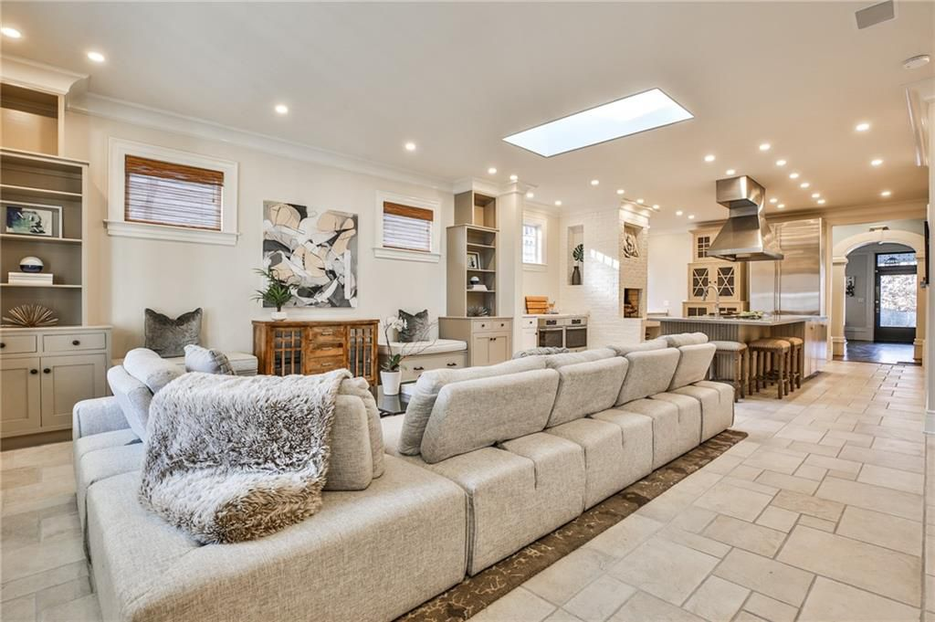 A large white living room with a skylight above it.