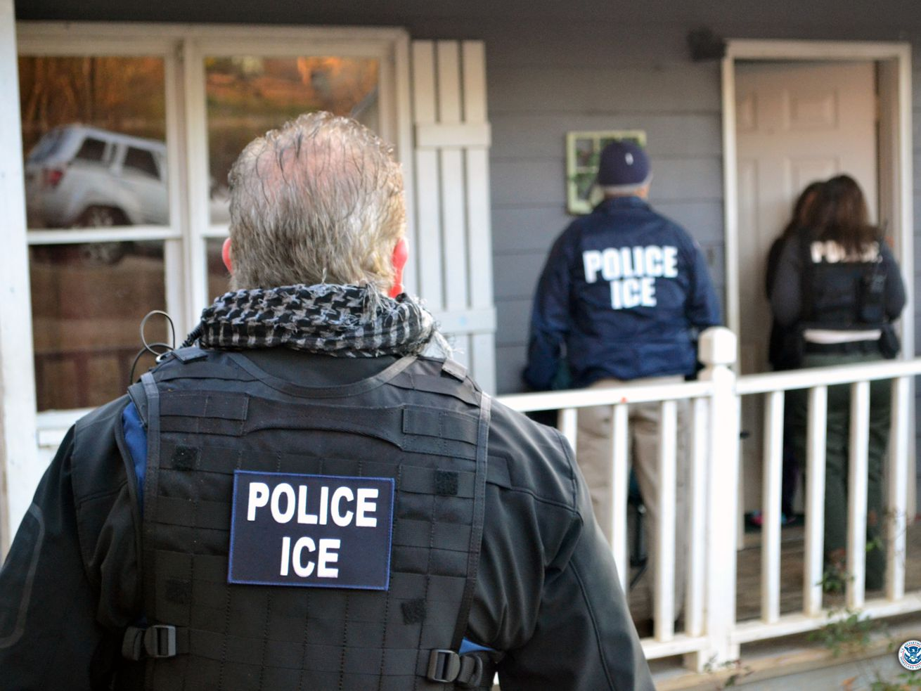 "Three agents with ""Police ICE"" jackets prepare to enter the front door of a residential property."