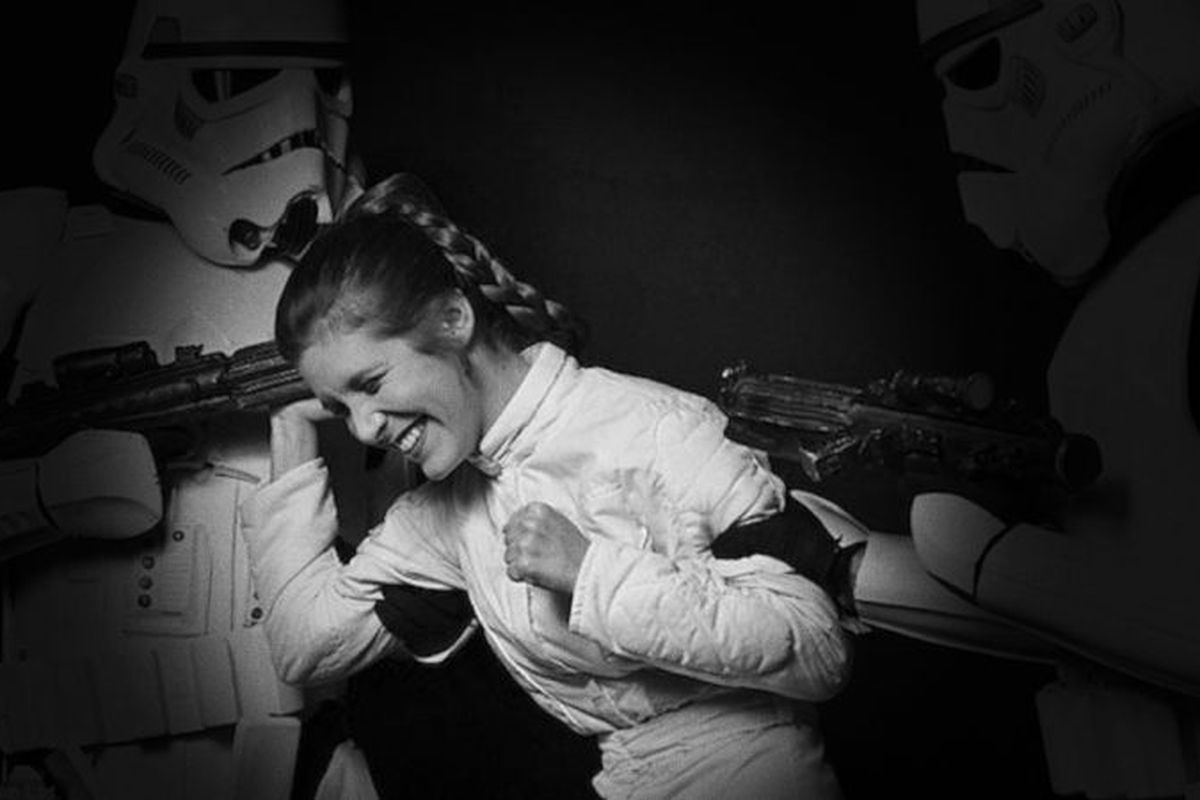 black and white photo of Fisher dressed as Princess Leia, laughing, with two people dressed as storm troopers from the movie holding her arms