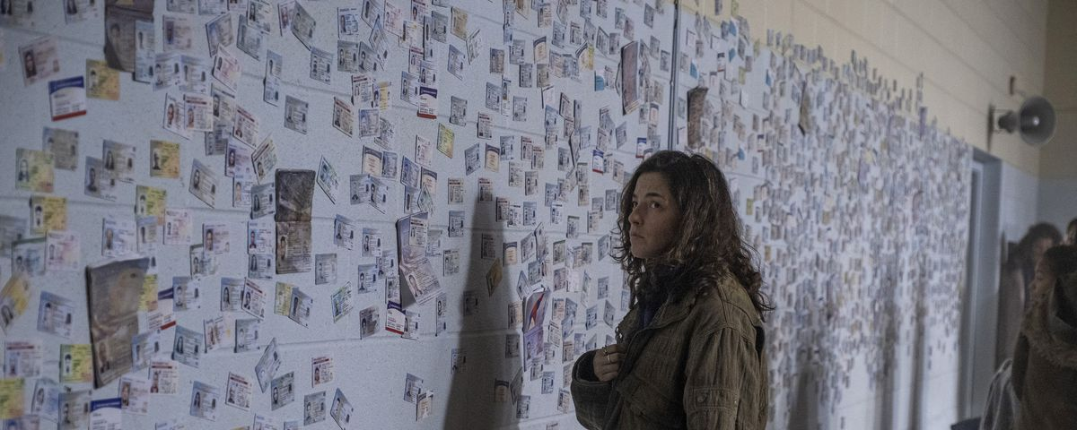 Hero Brown stands in front of a wall memorializing all the men who died in the FX on Hulu series Y: The Last Man.