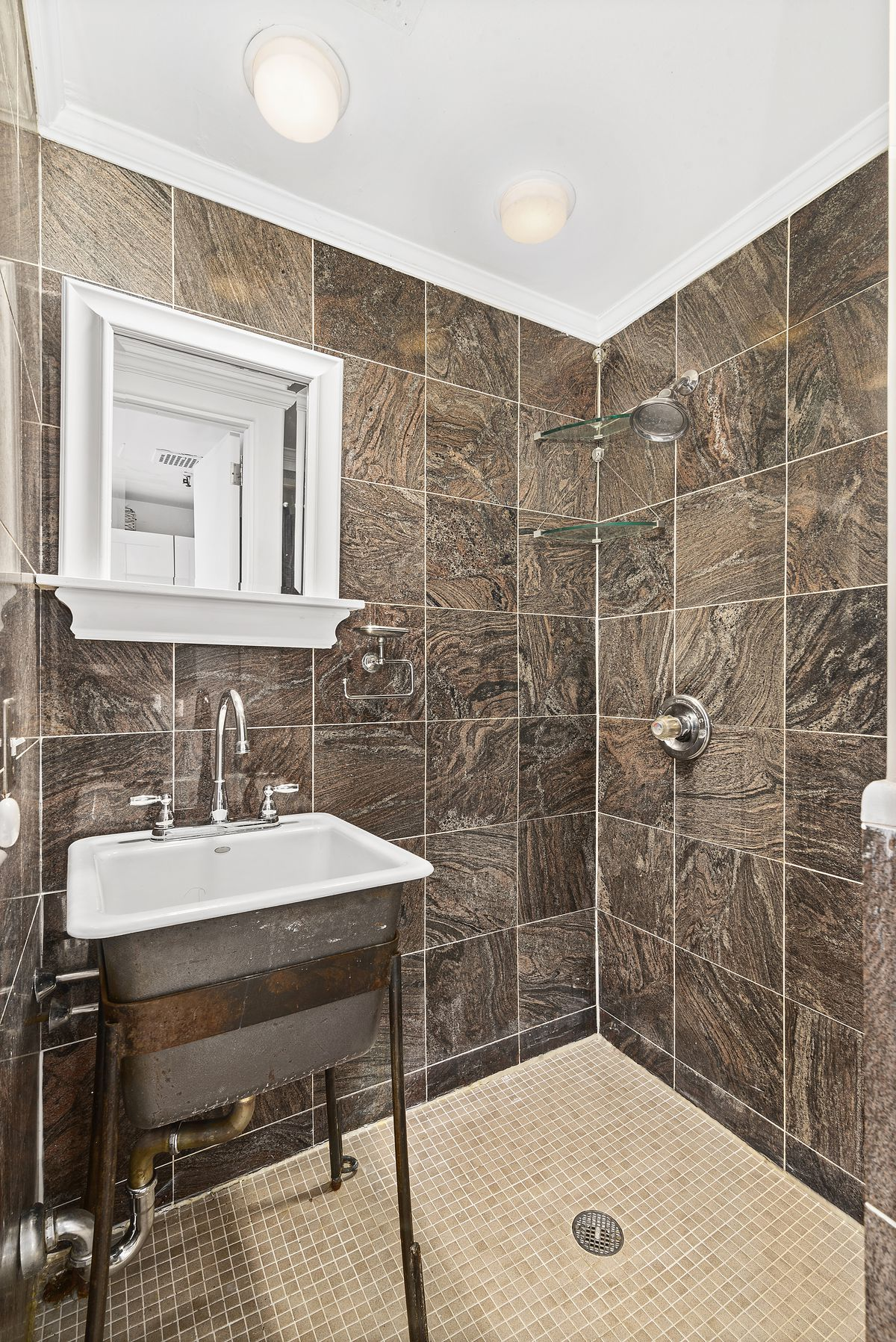 A bathroom with brown tiles.