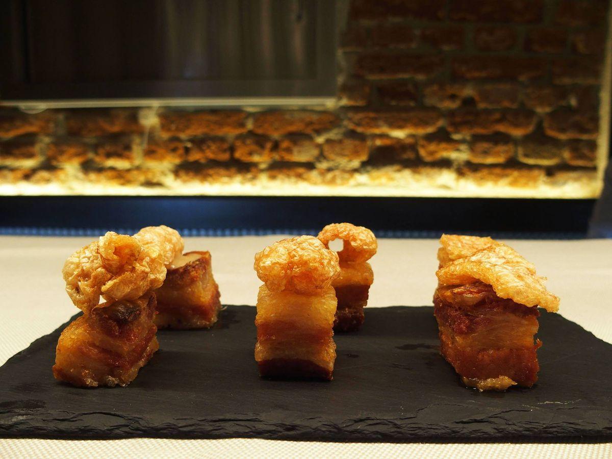 Six pieces of torreznos (pork rinds) arranged on a dark plate