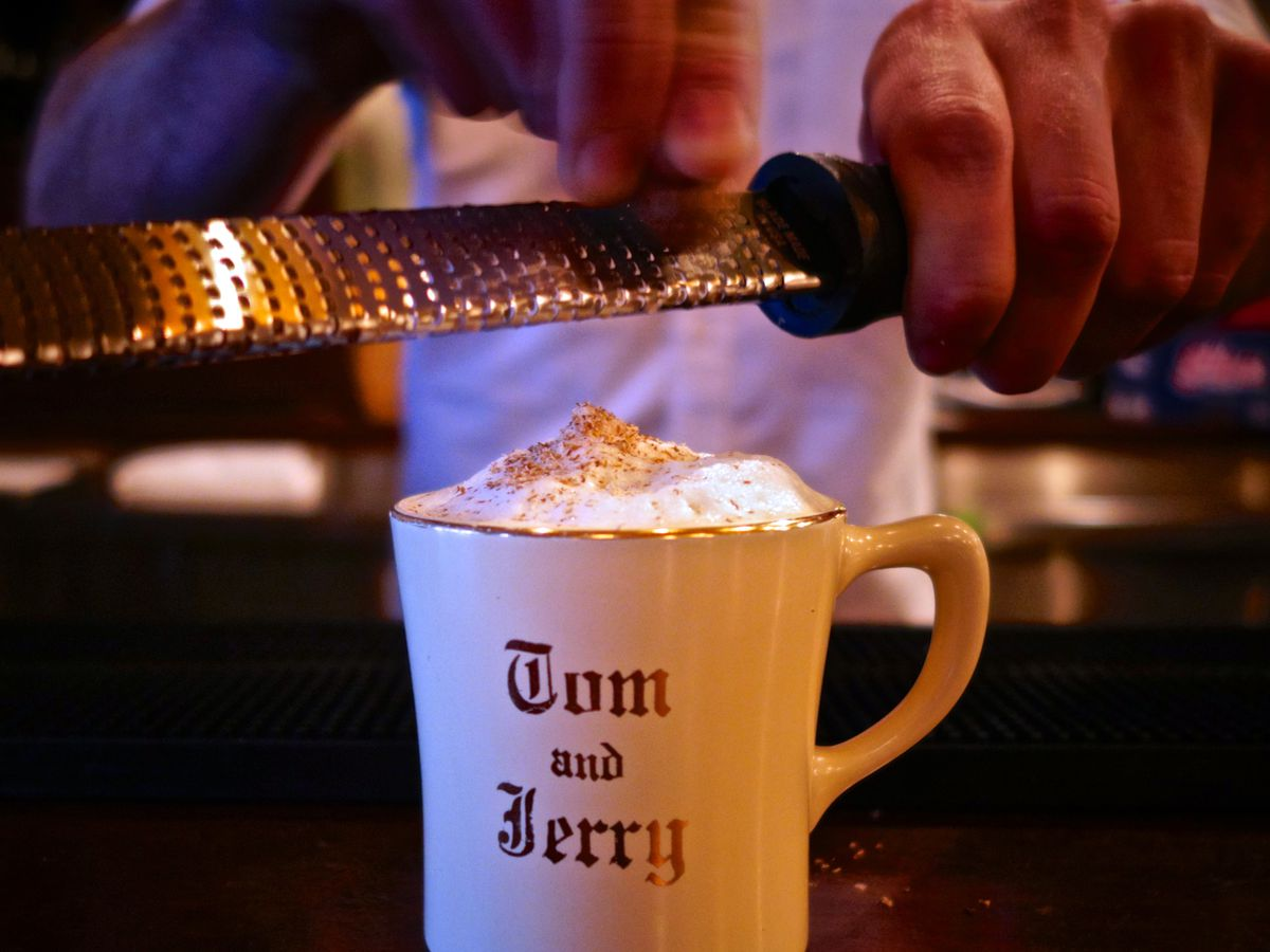 A bartender's hands grate cinnamon over a hot cocktail in a white Tom and Jerry mug