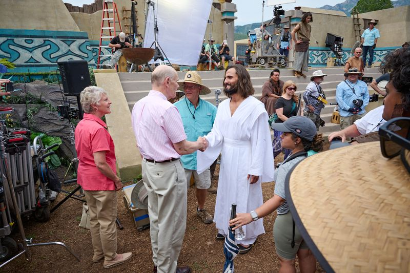 Elder Dale G. Renlund and his wife, Ruth, visit with cast and crew during the filming of the Book of Mormon videos series.