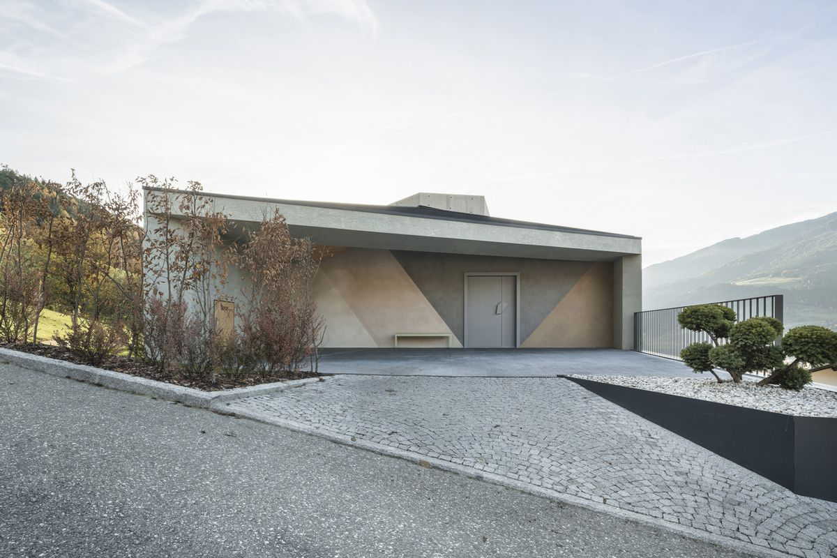 The exterior of a concrete house. The roof is flat and the front of house has a geometric pattern.