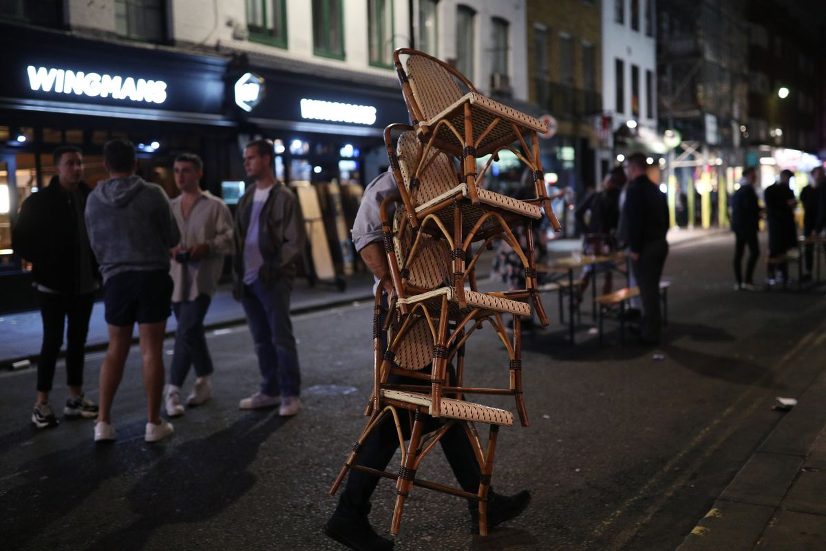 A London restaurant worker moves restaurant chairs off the street in Soho for the 10pm coronavirus curfew
