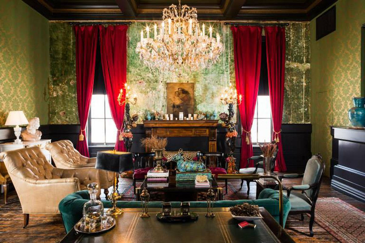 A lavish room in an 1800s building with restored walls, floors, and a huge chandelier