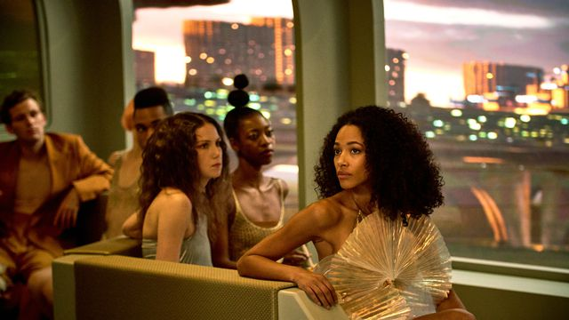 Kylie Bunbury and other cast members in gauzy future-garb sit by a window in Brave New World.