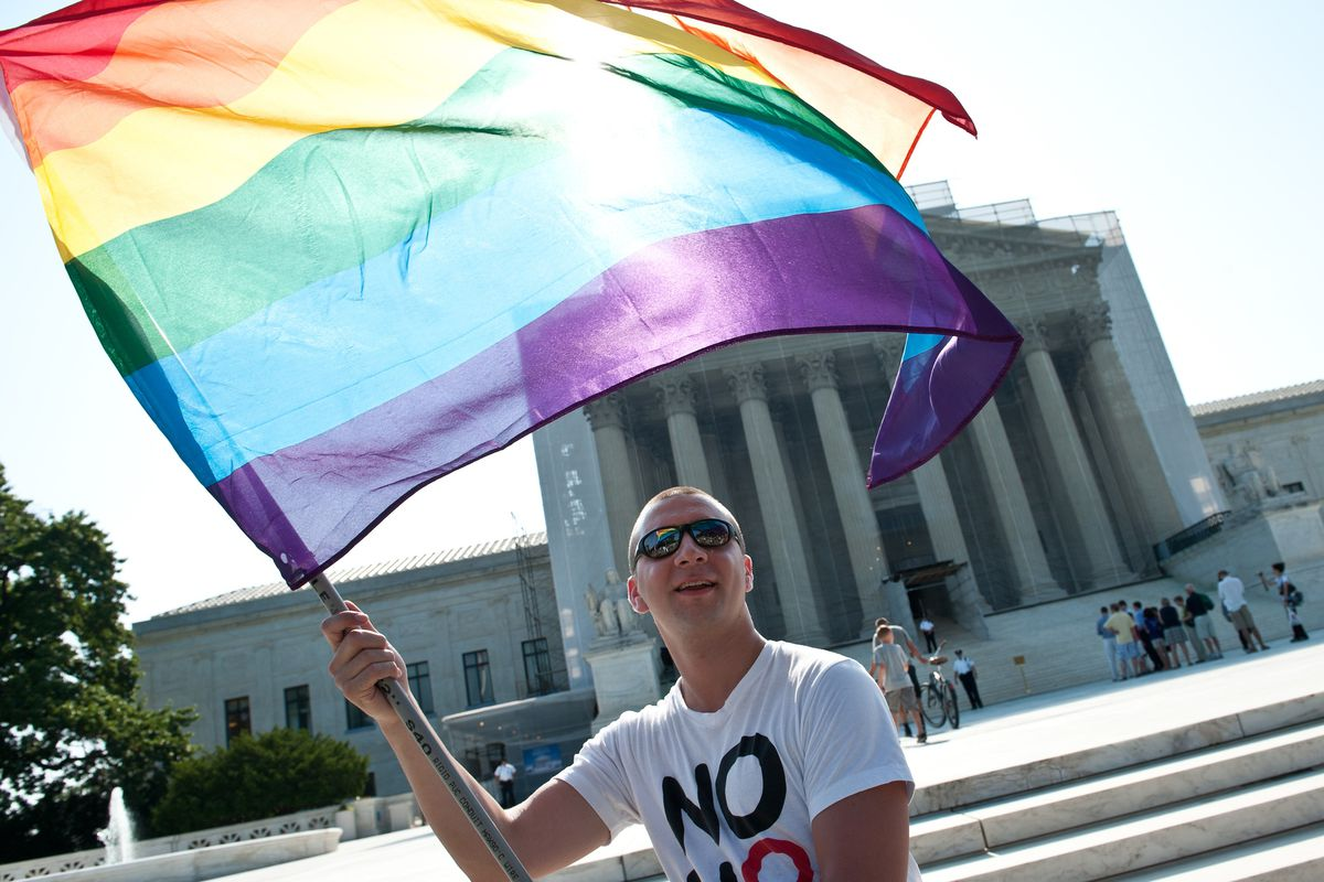 An advocate waves an LGBT Pride Flag in front of the Supreme Court.