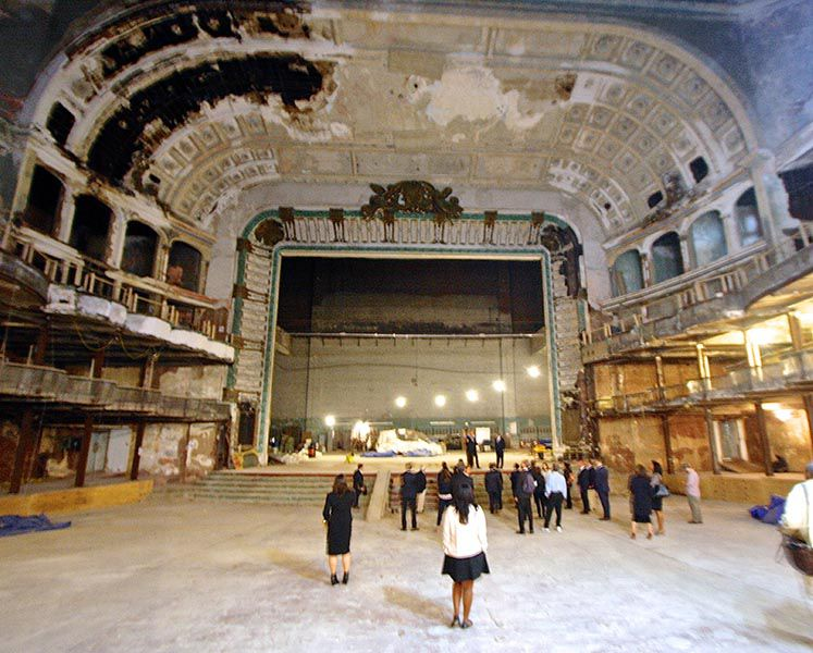 The interior of the Philadelphia Metropolitan Opera House. The building is abandoned. The walls are in decay. There are people standing on the ground floor.