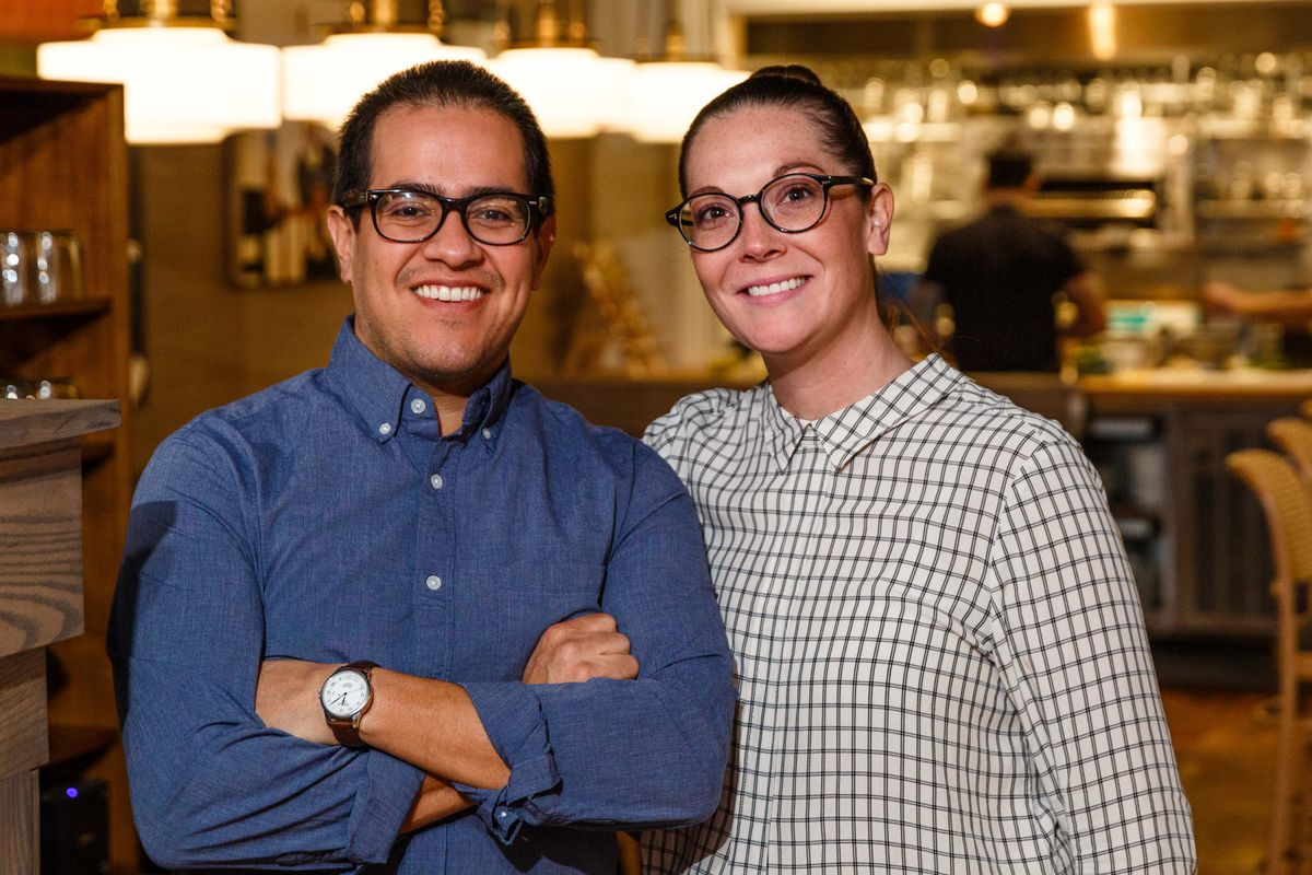 A man and a woman are smiling and standing next to each other in the photo. The man is dressed in a blue shirt and the woman in a checkered black and white shirt. Both are wearing glasses