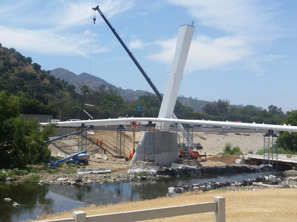 A tall white angled piece of the bridge rises out of a large concrete pier in the bed of the river. Two white beams bend over the pier and touch each bank of the riverbed.