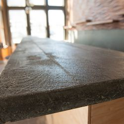 The concrete bar top was cast from a mold made from rough-sewn wood that was then sandblasted.