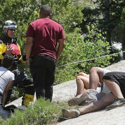 A member of the Salt Lake County Search and Rescue team talks with relatives of a 22-year-old hiker who fell in Bell Canyon falls as crews work to recover the body on Monday, June 5, 2017. Siaosi Brown's body was spotted in the lower falls of the canyon. His body was trapped on some logs in the middle of the waterfall, Unified Police Lt. Brian Lohrke said.