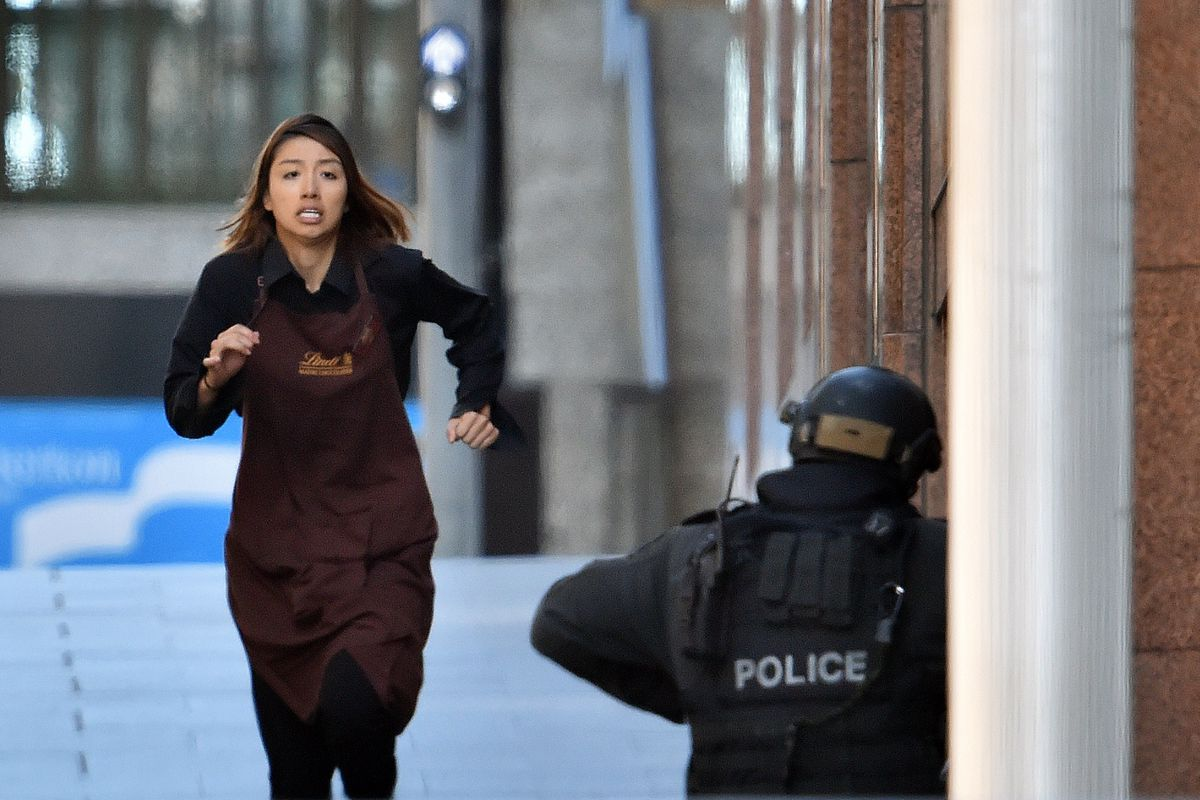 A captive runs out of Lindt cafe in Sydney.