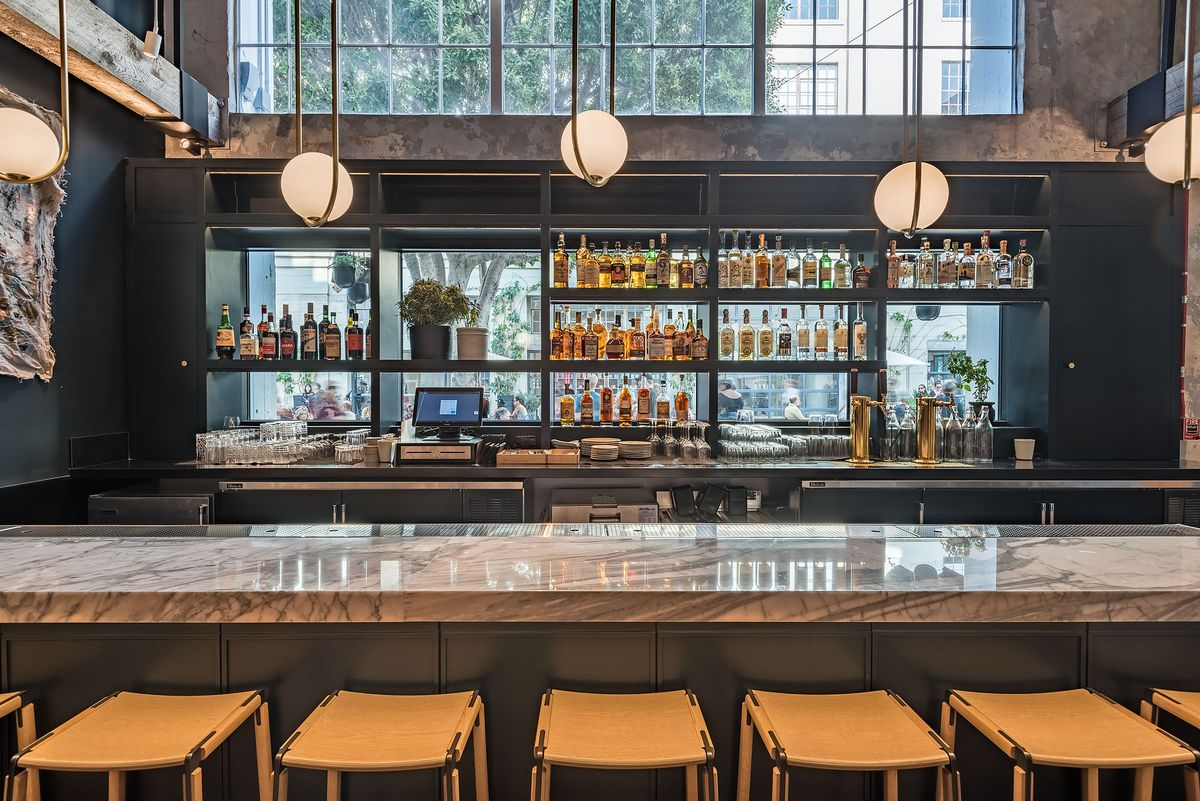Shiny marble bar seating with curved wooden backless stools.