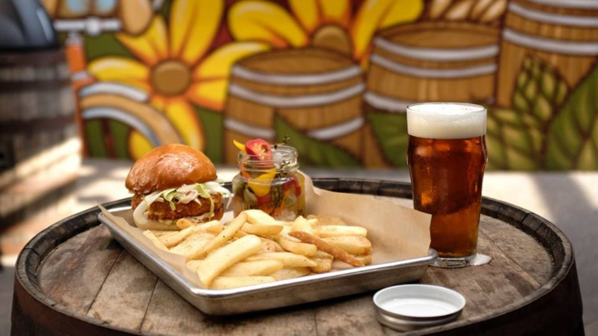 A tray with a big sandwich and fries on top of a barrel in front of an Adam Turman mural that was the side of Butcher and the Boar. The mural shows yellow flowers and barrels