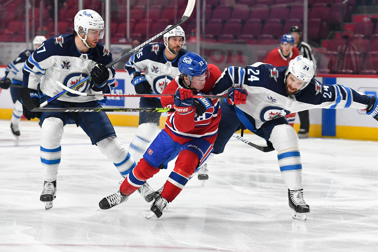 Cole Caufield battles Derek Forbort in game four of the Stanley Cup Playoffs between the Montreal Canadiens and the Winnipeg Jets.