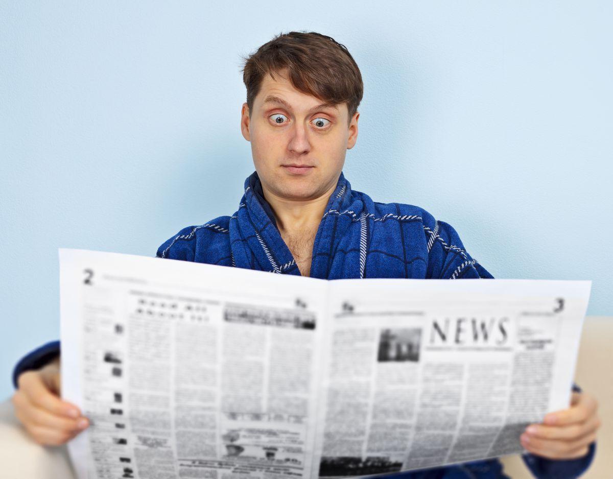 Very surprised man reading newspaper
