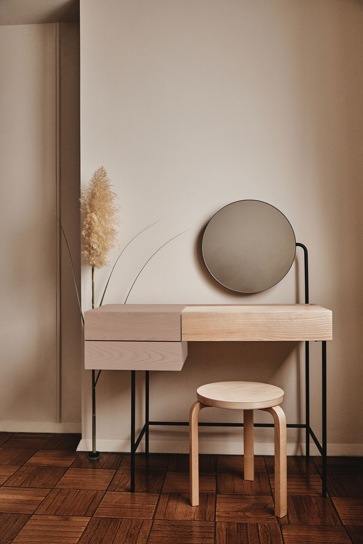 A pale wood desk with blush drawers and a round mirror.