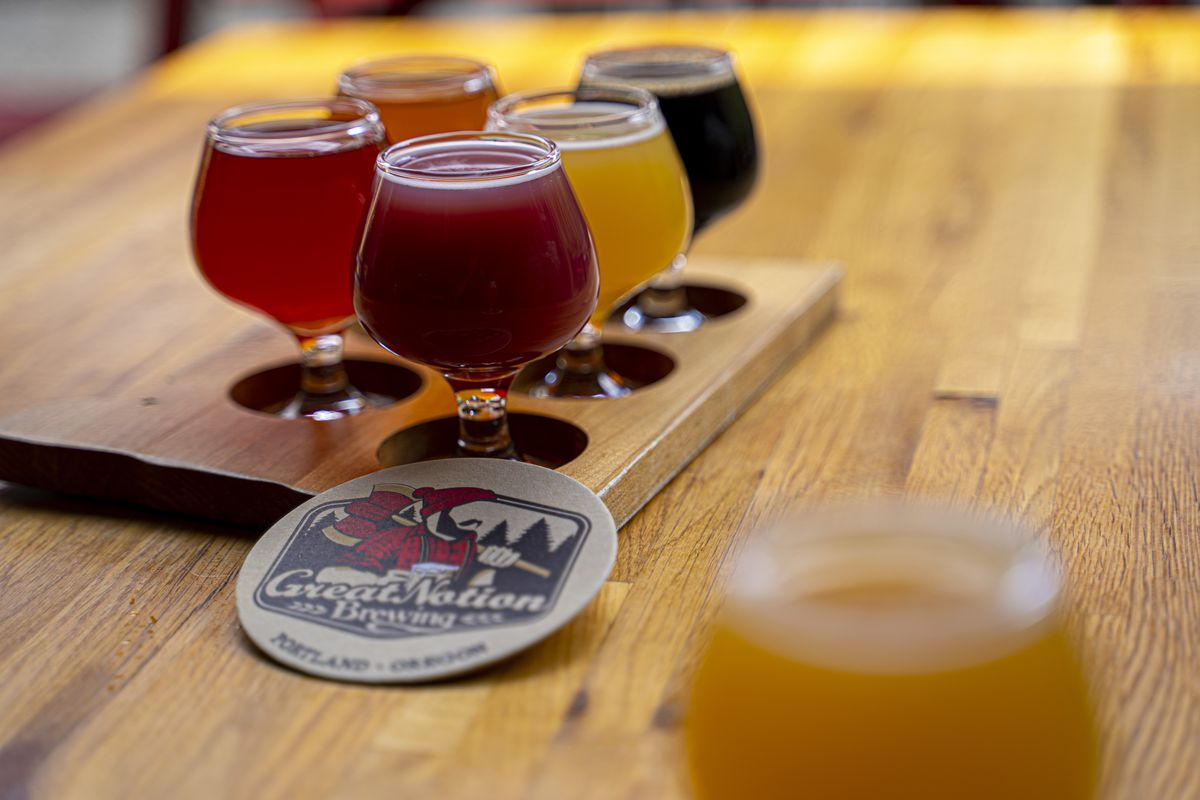 A variety of Great Notion beers in small 10-ounce goblets displayed on a light wooden bar.