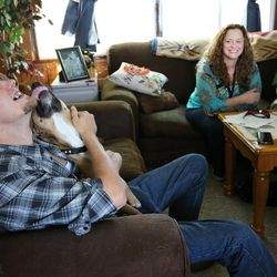Intensive Supervision client Shawn Myers, right, gets attention from his dog as Jeannie Ybarra, of Salt Lake County Criminal Justice Services, center and Salt Lake County deputy sheriff Jason Berg talk with him at his home in Salt Lake City on Thursday, Oct. 6, 2016.
