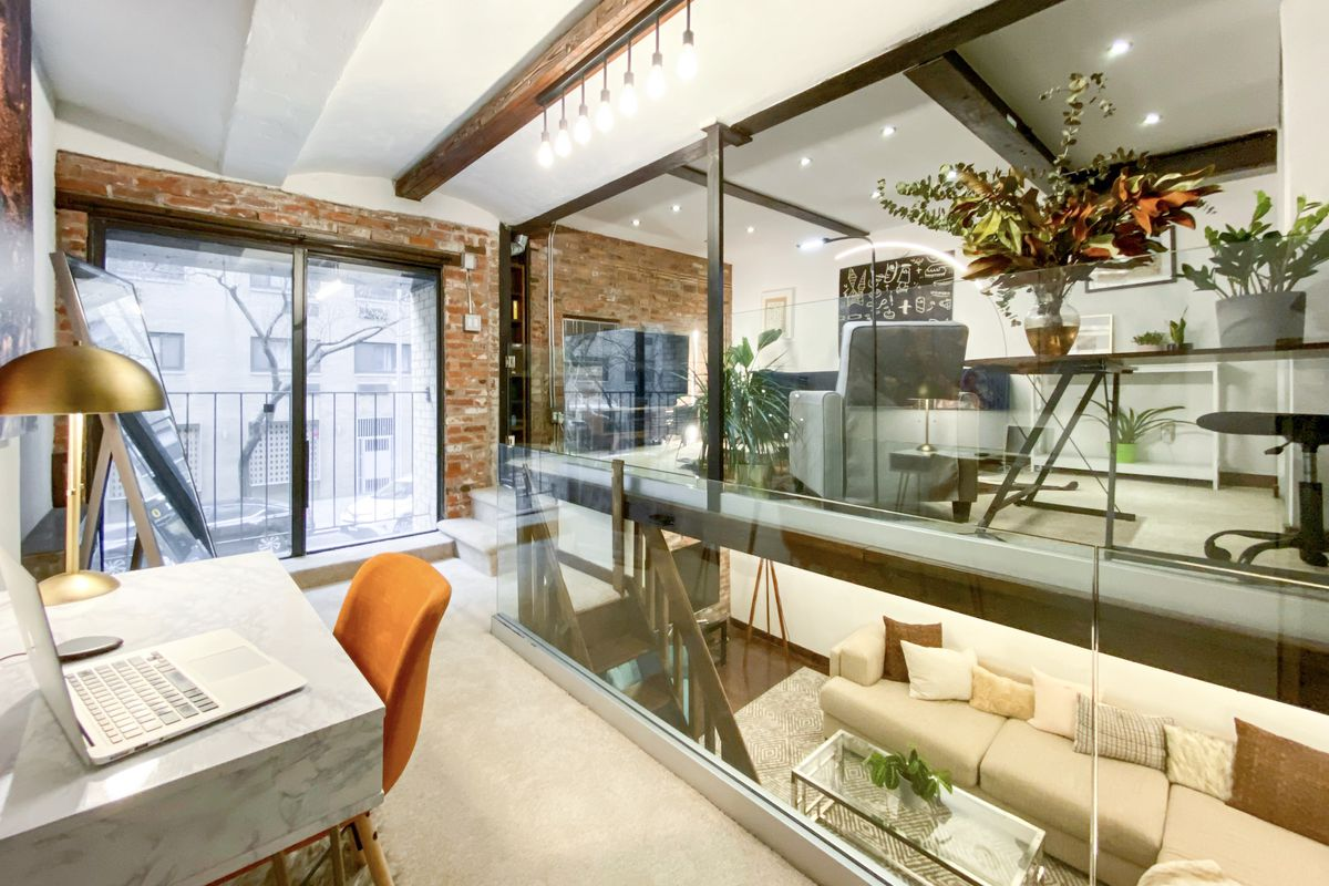 An office nook with exposed brick, a glass wall, and a Juliet balcony in the back.