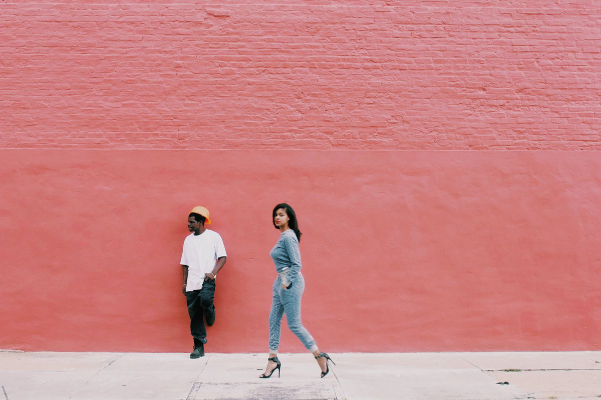 A fashionable woman walks by a construction worker against a painted brick wall.