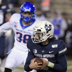 Utah State quarterback Henry Colombi runs with the ball as Boise State linebacker Demitri Washington (38) defends during the second half of an NCAA college football game Saturday, Nov. 23, 2019, in Logan, Utah.